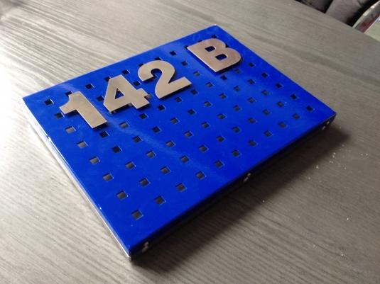 Lackerad plåt med stansade hål, rostfria bokstäver på distans.