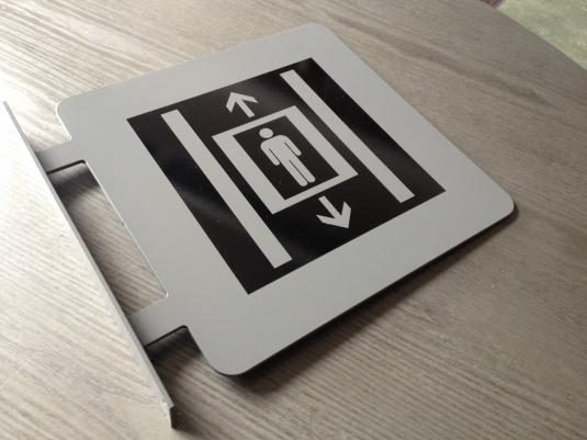 Digitalfräst plåtskylt. 5mm aluminiumplåt som vi har pulverlackerat med symbol i folie.