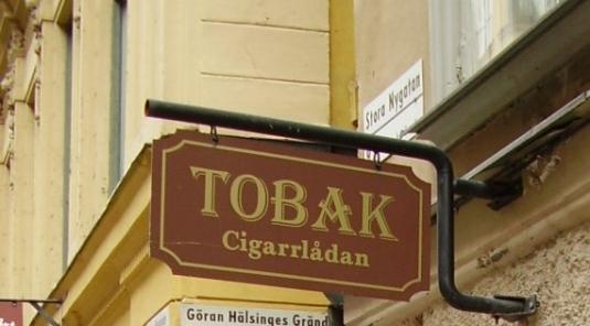 Tobak Cigarrlådan : Smidesstativ och plåtskylt i Gamla stan.