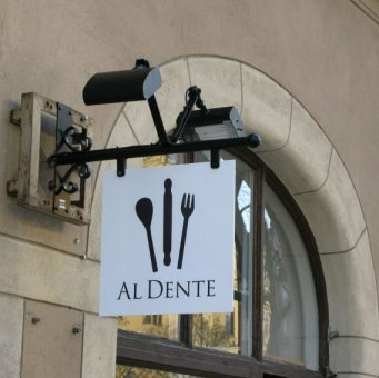Al Dente: Vi har tillverkat en smidesskylt med PL-strålkastare till Al Dente. Bottenplåten görs av 3mm aluminiumplåt som vitlackeras. Logon i svart vinylfolie.