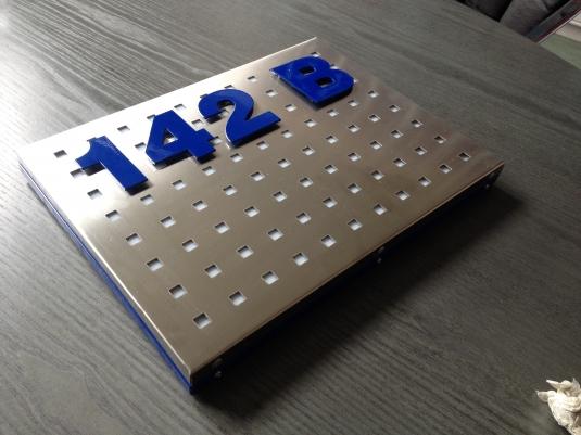 Stansad rostfri bakrundsplåt med bokstäver på distans.