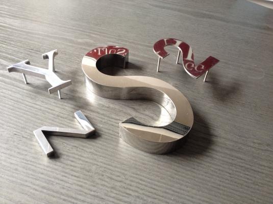 Blankpolerade rostfria bokstäver, med kant eller plana. Distansstift monteras på baksidan.